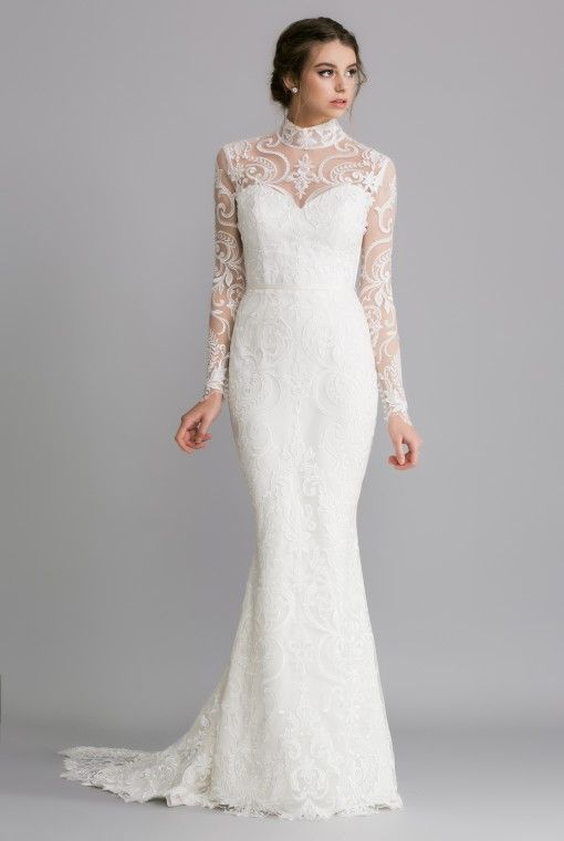OCA624T SIENNA  An allover lace gown with full length sleeves and high collar, the sheer embroidered lace detailing sits over a satin under-dress and is finished with a satin sash at the waist.
