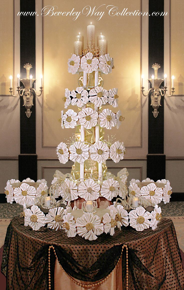 """Floral Fantasy - This design shimmers and sparkles. One solitary round cake of this design, a beautiful crystal stand, and a beautiful draping tablecloth would be suitable for gracing a small wedding or affair. Seven of the ten cakes for this idea are covered in caramel colored fondant and three cakes are covered in black fondant. Each tiered cake is a 4""""H oval, and the surrounding accent table cakes are 4""""H rounds. The pleated flowers are dried fondant. Centers are wired gold ..."""
