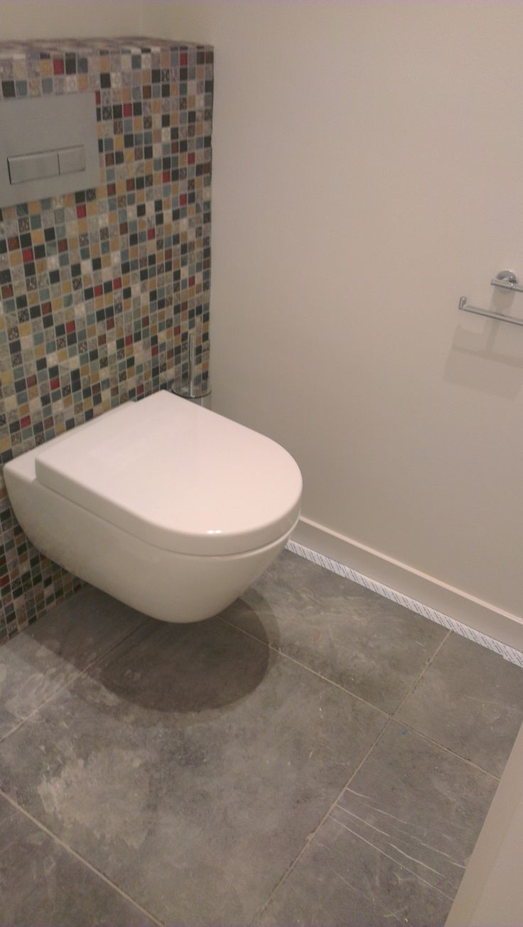 Toilet met moziek op de achterwand en een hardstenen vloer, in combinatie met stucwerk.