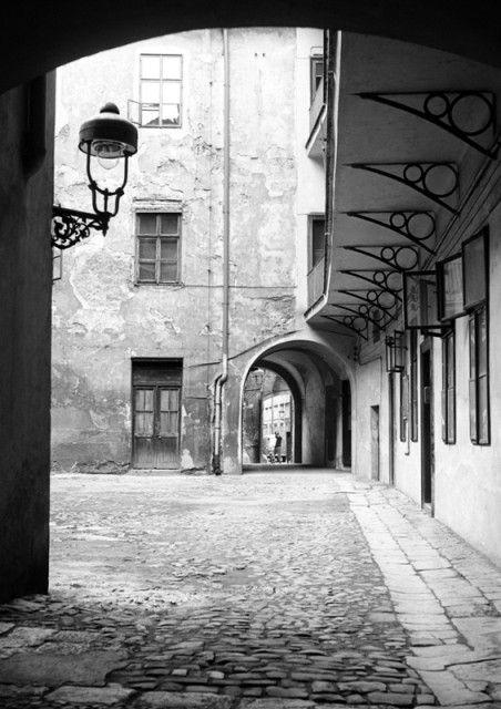 Část dvora pavlačového domu (1238) • Praha, 1961 • | černobílá fotografie, průchozí dvůr mezi Liliovou a Řetězovou ulicí, dlažba, lucerna, loubí, průchod |•|black and white photograph, Prague|
