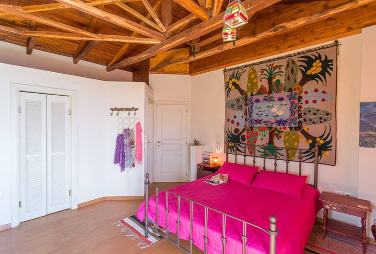 UPPER FLOOR / Bedroom 1 with ensuite bathroom: naive colorful hand-woven textile on the wall ...