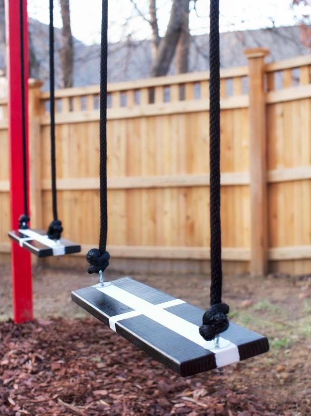 This chic DIY swing set features graphic black and white swing seats, black nylon rope and a red frame.
