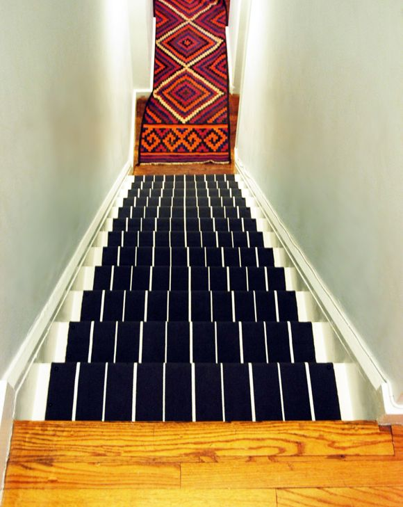 Jenny of Little Green Notebook ripped the old carpet off her stairs and painted them white. After adding rug pads to the tops of the steps, she made a runner out of four IKEA rugs and a brad gun. See her step-by-step guide »   - HouseBeautiful.com