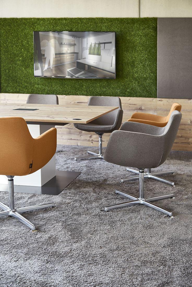 Orange in Kombination mit einem warmen Grau und Grasgrün sorgt für eine einladende und gemütliche Atmosphäre im Konferenzraum.