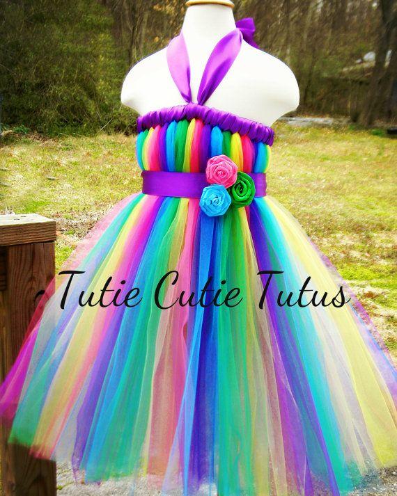 Bienvenue sur Tutie Cutie Tutus !  Cest tellement coloré et beau!!! Cette robe tutu est super adorable, quil est parfait pour, des photographies, des anniversaires, des mariages ou des habille ! Cette robe est faite avec plus de 100 yards de tulle vibrant mou de Kelly Green, goyave, Malibu Blue, rayon de soleil jaune et violet Regency. La face avant dispose de belles roses satin attachés à une ceinture de ruban de satin violet. Licou. Robe a également satin tout de suite autour de la…