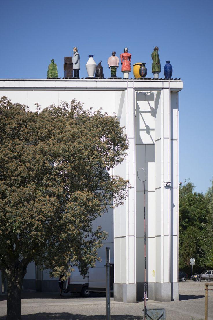 #Lübeck Eine Frau, zwei Männer und ein Kind mit verschiedenen Gepäckstücken stehen nebeneinander auf dem Dach der Kongresshalle. Sie stehen allerdings jeder für sich und in sich gekehrt.Die Figurengruppe ...