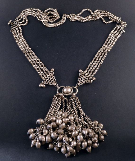 This is an extraordinary and heavy old tribal necklace from Rajasthan, made with high grade silver. The chain was handmade with 4 lines, small dangles and flower silver beads to join the different parts of the necklace. It ends up in a silver botton with 2 chains pendants with a several mango shape silver pendants at the end. It is and old and worn item.