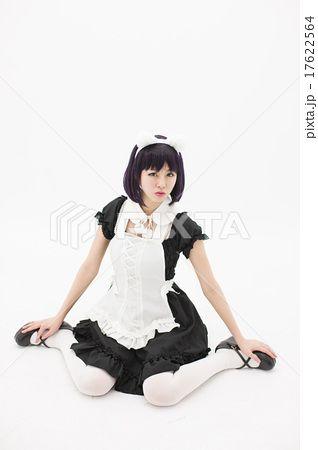 白い背景の前で女の子座りをしているメイド姿の若い女性