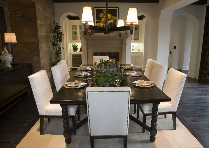 Open concept home with designated dining area in front of fireplace. Dark wood dining table and eight white chairs sitting on large rectangle white rug on top of dark wood floor.