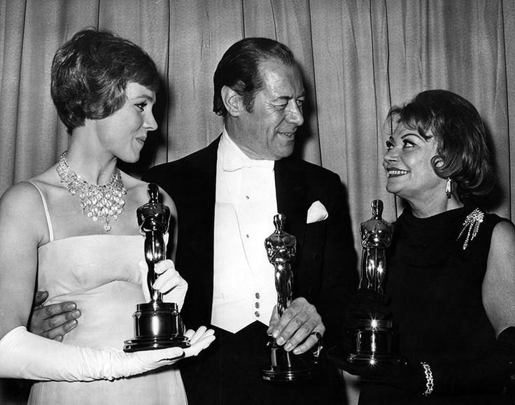"Photograph caption dated April 6, 1965 reads, ""Winner's circle - Julie Andrews, best actress; Rex Harrison, best actor, and Lila Kedrova, best supporting actress, clutch their coveted Oscars after last night's 37th annual Academy Award spectacle in Santa Monica Civic Auditorium."""