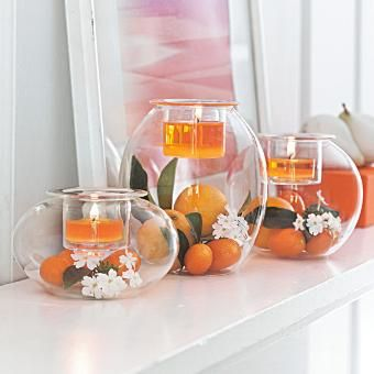 """Three shapely blown glass holders to fill with your own decorative touches! Top with a votive or tealight, sold separately, in the pressed glass votive cup. One each: 5¼""""h, 4""""h, 2¾""""h. White flowers, oranges, green leaves, orange votive candles, trio centerpiece, weddings, party ideas, home decor"""