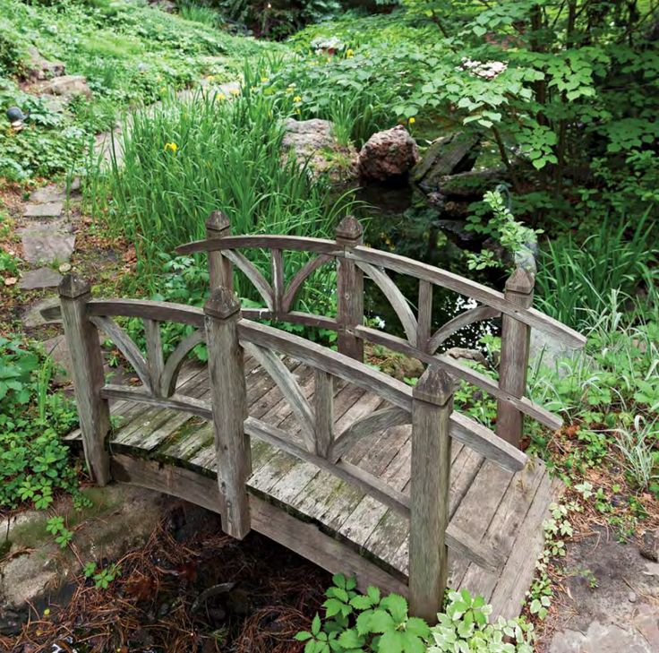 A Wooden Bridge Spans Babbling Brook The Arcing Handrails Echo Pleasing Curve Underfoot