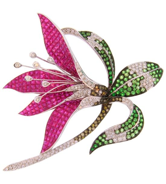 Ruby, tsavorite garnet, diamond and 18 karat white gold brooch, in the shape of a flower, with 235 fancy cut and invisibly set rubies weighing 7.00 carats, 109 round tsavorite garnets weighing 3.00 carats and 169 round white and brown diamonds weighing 3.50 carats.