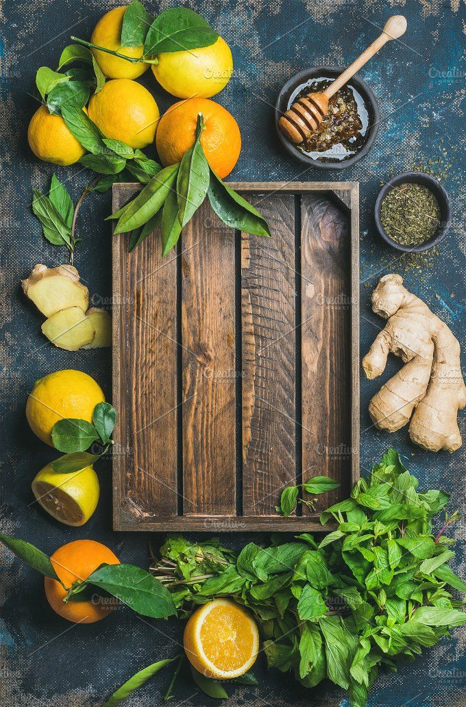 #Ingredients for natural hot drink  Ingredients for making natural hot drink with wooden tray in center. Oranges mint lemons ginger honey apple over plywood background top view copy space. Clean eating detox dieting concept