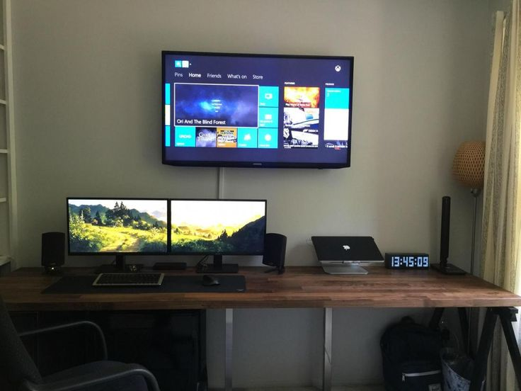 Dual monitors on wooden desk with wall mounted TV. 10