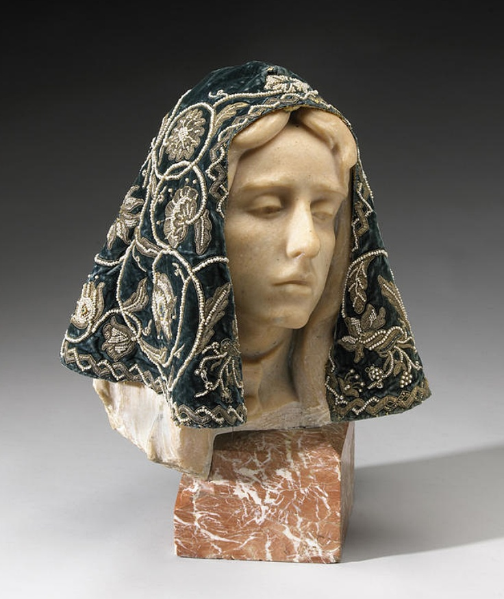 A fine and rare metallic thread and jeweled hood  Iberian or Austrian  late 16th century  Applied with scrolling flowering plants springing from a late Renaissance urn in metallic thread and enriched with seed pearls, the flower heads centering Renaissance gold and enameled jewels set with precious stones including rubies and emeralds, the initials for the Virgin Mary beneath the crown on the back of the head above the urn.  height 12 1/2in (31.5cm)