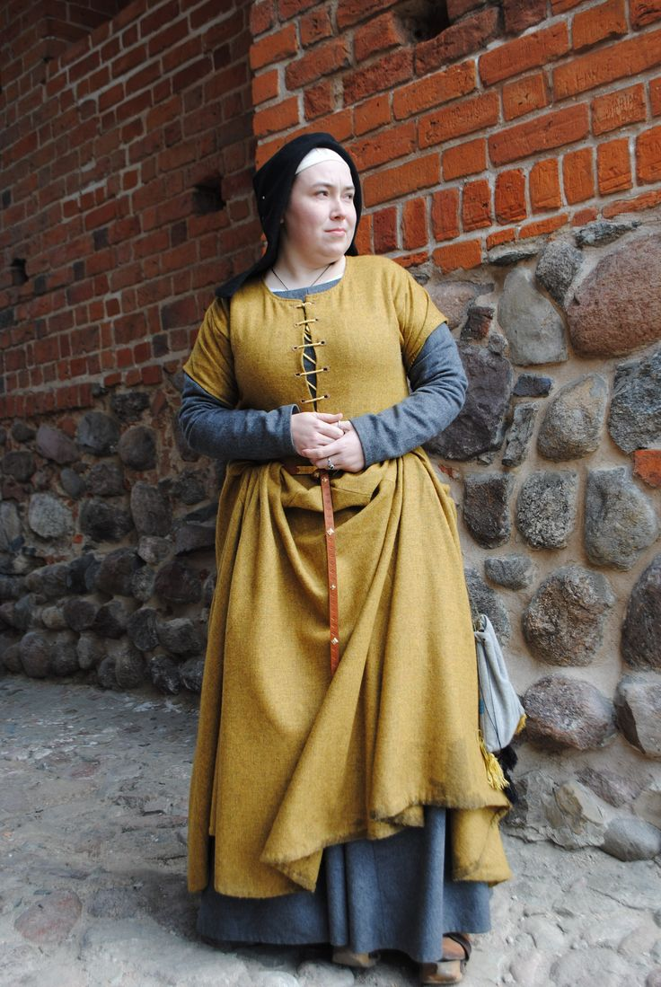 Medieval outfit based on Flemish illuminations from the 1st half of the 15th century, depicting women in town. Linen chemise, woollen hose, leather shoes, cotte simple of grey wool and over kirtle of yellowish-orange wool, linen st Birgitte's cap, open hood of black wool, girdle with accessories. All part completely hand-sewn. Here, revealing a bit more of the underdress