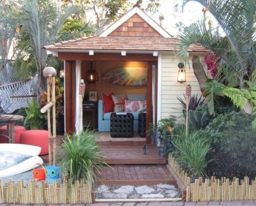 Playhouse with tropical landscape, hammock and tiki torches.