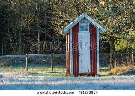 Ronneby, Sweden - January 7, 2018: Documentary of everyday life and environment. Small outdoor dry toilet or outhouse with fence and forest in background. Cold day with frost in the grass.