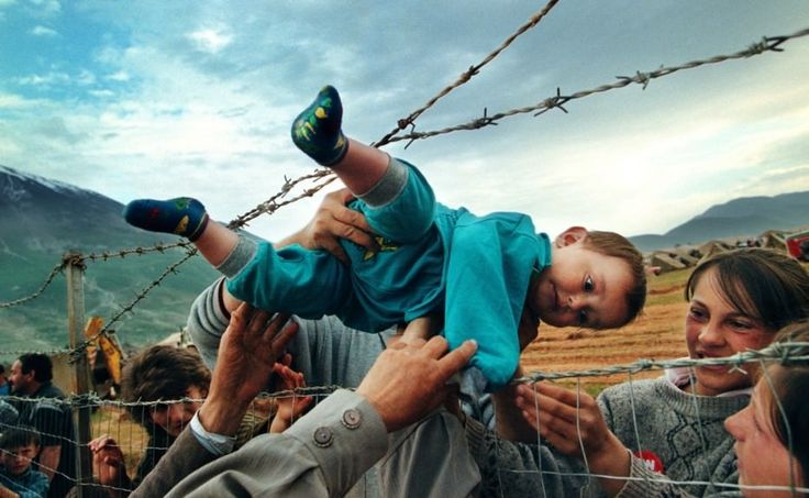 A child is passed through barbed wire to his grandparents at a refugee camp during the Kosovo War.