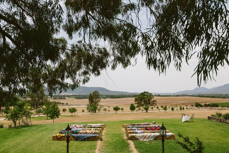 Embracing the Hunter Valley vibe with hay bail seating and vintage rugs for this open air wedding ceremony | PHOTO CREDIT: Cavanagh Photography - @cavanaghphotog
