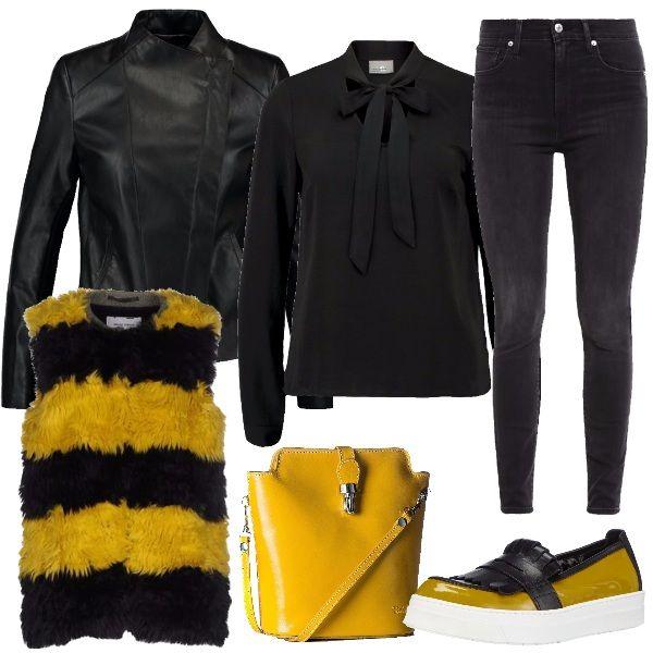 Outfit composto dalla camicia nera con il fiocco, la giacca in ecopelle nera, abbinata al gilet in eco pelliccia a righe gialle e nere e al jeans skinny grigio scuro. Completano la tracolla gialla e la slip on nera e gialla con frangia nella parte superiore.