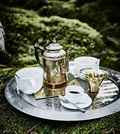 A metal tray with cups of tea, coffee and a kettle resting on the ground in a forest wedding lounge