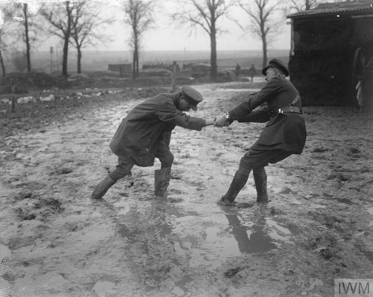 Two officers struggling through a muddy field near Arras, 19 January 1918.