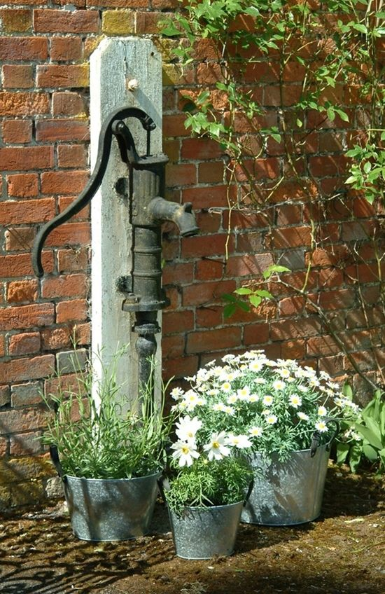 Old hand pump by three galvanized planters- I could do this with my pump.
