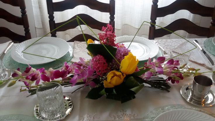 Centrotavola floreale con giacinti rosa, tulipani gialli e orchidee rosa. Tavola total white con tovaglia di fiandra, sottopiatti in cristallo, piatti in porcellana bianca, bicchieri tumbler di cristallo con sottobicchiere d'argento, posate d'argento.