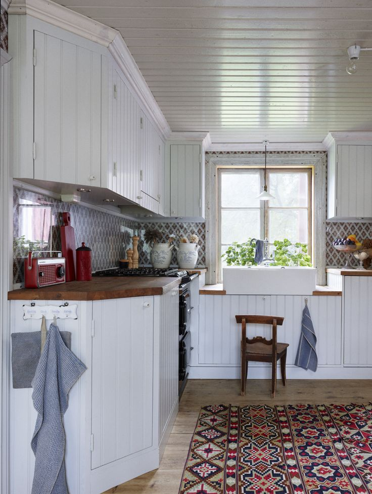 Köket med specialinredning i gammal stil. Bakom stänkskyddet i härdat glas syns tapeten Näskotts hembygdsgård från Handtryckta tapeter. På golvet en gammaldags allmogebonad  köpt på nätauktion.