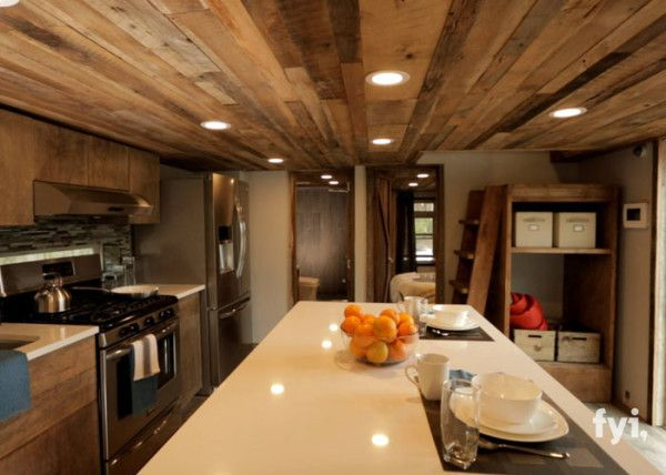The spacious kitchen is capped by a ceiling consisting of paneling from reclaimed wood, which gives the room a rustic vibe offset cleverly by sleek, stainless steel appliances.