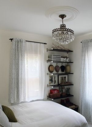 Small bedroom. Open shelving in corner, floor to ceiling. Light bedding, curtains