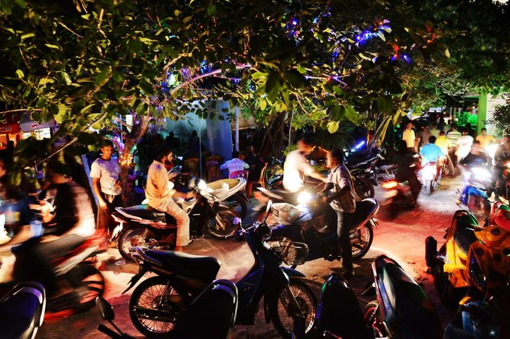 NIGHT CRUISERS: Residents of Malé, the capital of Maldives, used mopeds to drive past a popular nightspot Wednesday. (Roberto Schmidt/AFP/Getty Images)
