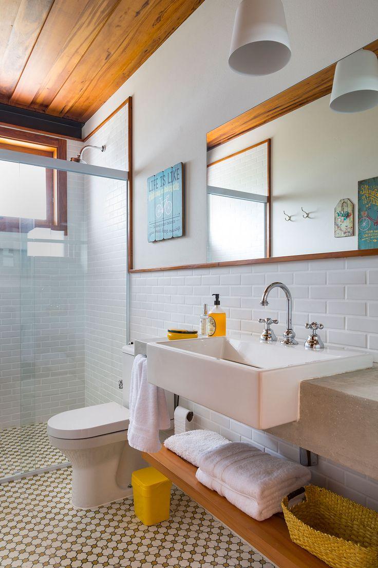 Decoração de casa de campo com madeira. No banheiro decoração neutra com prateleira de madeira, parede de tijolinho branco e detalhes amarelos.