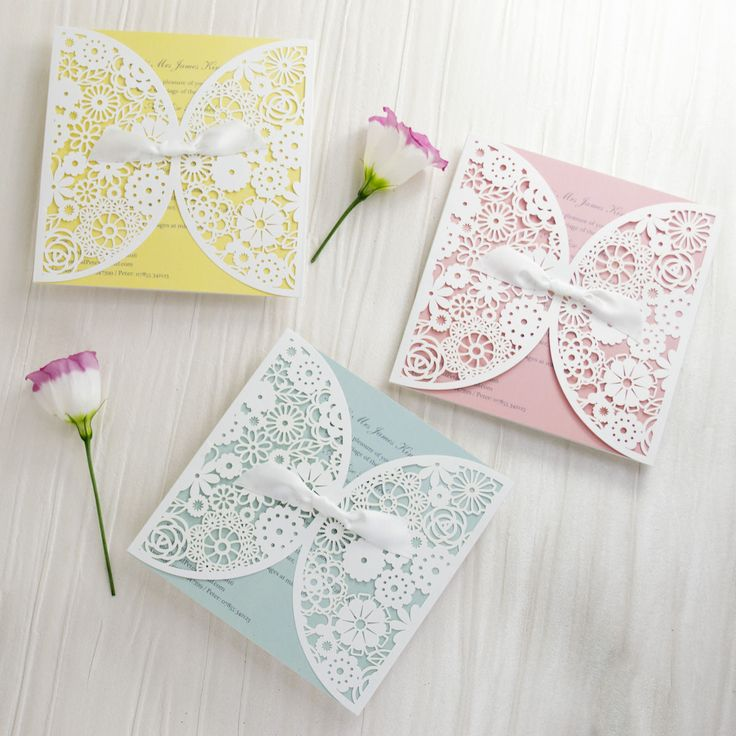 Personalised lace vintage-style laser cut wedding invitations, with pink, blue and yellow inserts.