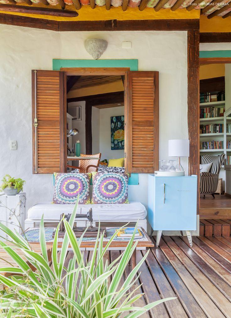 Varanda tem sofá feito com pallets, mesa de centro de madeira e frigobar retrô.