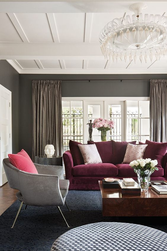 Love the rich pink and burgundy accents in this gray and white living room.