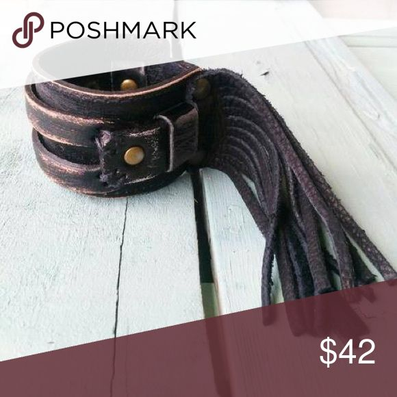 """Brown Distressed Fringe Cuff Each hand-distressed cuff is made with genuine leather and features two adjustable snaps. Entire length of bracelet is 2"""" by 9"""".  Adjusts with snaps from Approx. 7"""" to 7.5"""".  This high quality, hand-crafted jewelry is made right here in Texas. These unique pieces are created by hand so no two cuffs will look the same. Expected delivery date is November 20th. Pre-order yours today! Jewelry Bracelets"""
