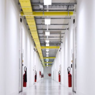 A corridor running between server rooms (in the Amsterdam facility) features overhead cable trays and, of course, fire extinguishers.