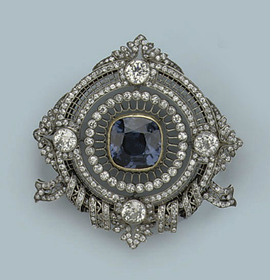A BELLE EPOQUE SPINEL AND DIAMOND BROOCH Designed as a finely pierced circular front pavé-set with numerous circular-cut diamonds, centering a large cushion-shaped blue spinel, four larger diamonds set at the cardinal points, the base with scrolled bow motifs, circa 1910