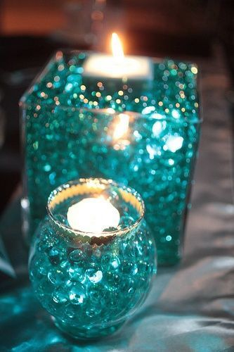 Glass, Candles and Beads Centerpiece -  these look like marbles, but they are actually water beads that are used to in arrangements to help regulate water. Easily accessible at most craft stores, these jelly like beads come in several shapes and colors.