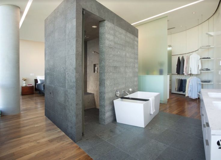 This concrete privacy cubicle provides a division from bedroom to bathroom whilst maintaining the bath and vanity as features. I particularly like the grey floor tile connection to the walls. This space would suit industrial style  Photo credit- Altus Architecture and Design