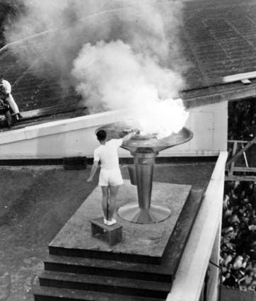 Olympic Games, Melbourne, 1956. 19 year old Australian track athlete Ron Clarke, who set 17 world records during his running career, lights the Olympic flame at the opening ceremony of the 1956 Melbourne Olympics. Photographer: J. Fitzpatrick. NAA: A7135, 05/23A