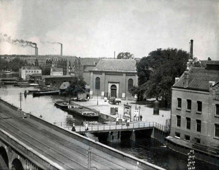 1911 Bickerseiland Gezicht op Bickerseiland met fabriekjes, schoorstenen, schepen en een autoweg.