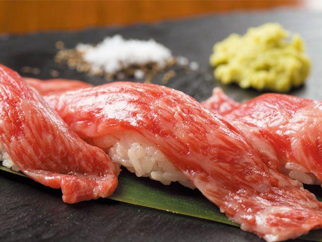 《 池袋 》霜降りの上質なサーロインを魅惑の肉寿司で『肉寿司と手作りチーズのお店 NIKU BAR KACCHAN』  池袋  「黒毛和牛を使った寿司」と聞いて、どのような店を思い浮かべるだろうか。老舗の肉割烹や肉問屋直営店、はたまた高級な和牛専門店が浮かんだ人も多いだろう。2015年10月、池袋にオープンした『NIKU BAR KACCHAN』は上質な肉寿司を看板商品に据えながら、リーズナブルな価格設定と温かみのある接客で「若い人も気軽に入れる店」を目指している。   オーナーシェフの笠川大海氏がこだわるのは、適度な霜降りを持つA4ランクの岩手県産黒毛和牛。肉寿司を中心に、刺身やステーキ、カツレツなど幅広い肉料理を用意しているのも『KACCHAN』流だ。