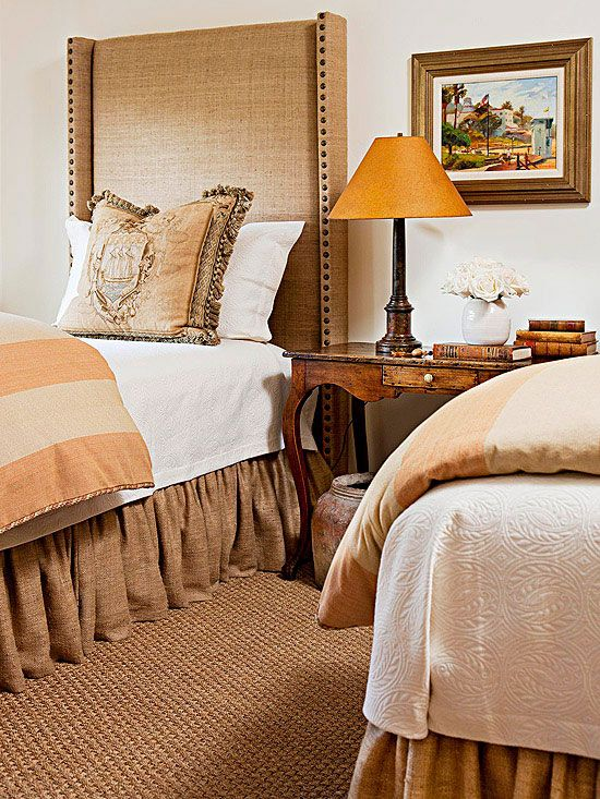 Rustic Charm - Part of the appeal of old-world styles is the rough-edged quality. Modern creature comforts, however, are something few would give up for the sake of authenticity. In this bedroom, coarsely woven fabrics in earthy tones cover the tall headboards and drape to the floor as bed skirts. The bedding is tightly woven modern material for comfort.