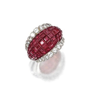 MYSTERY-SET RUBY AND DIAMOND RING, VAN CLEEF & ARPELS, NEW YORK.  Of bombé form, mystery-set with numerous square-cut rubies within borders of 26 round diamonds weighing approximately 1.35 carats, mounted in platinum, size 5½, signed Van Cleef & Arpels, numbered N.Y. 47668. With pouch.