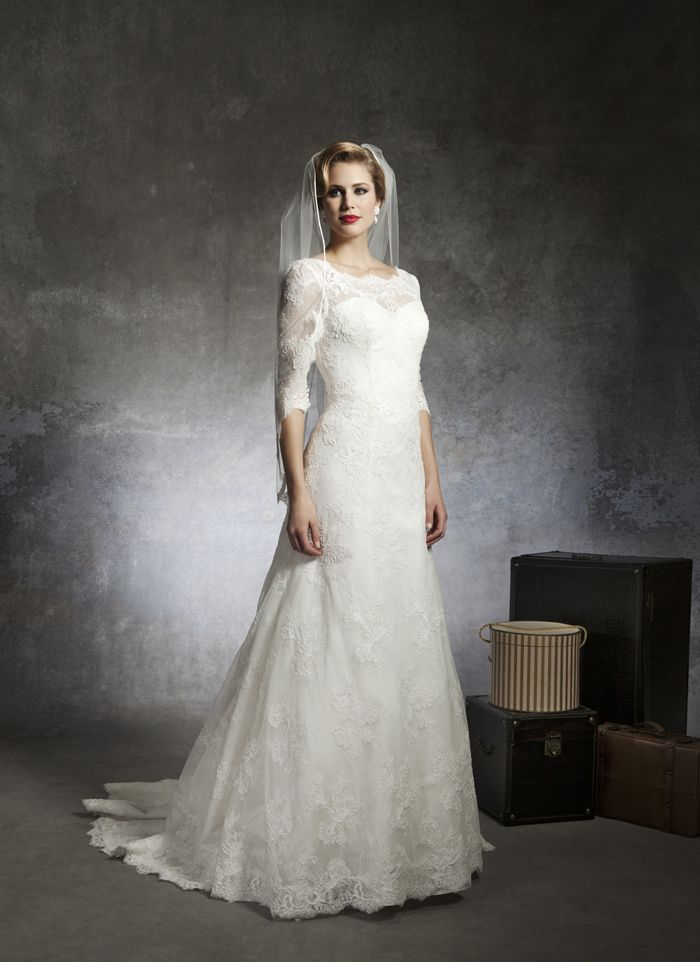 Justin Alexander wedding dresses style 8666 Sabrina Alencon lace neckline with 3 quarter length sleeves that accent  the drop waist and A-line skirt. Gown has a V-back, buttons that cover  the back zipper and the sweep length train.