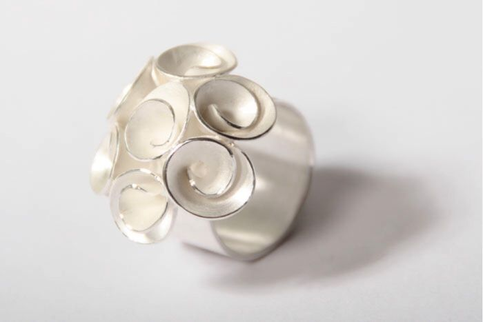 """Zilveren ring """"Marieke""""  De in 925 sterling zilveren damesring is een ambachtelijk en uniek met de hand vervaardigd exemplaar en bezet met zeven bloemen met een scala fijne details. Het exclusieve karakter van de ring wordt onderstreept door de matte finishing van het zilver. De 7 bloemen wordt door een in detail afgewerkte zetting bijeen gehouden. De ring komt uit een zilversmid collectie handgemaakte sieraden uit Azië. Binnendiameter van de ring-scheen 175 mm wat overeenkomt met ringmaat…"""